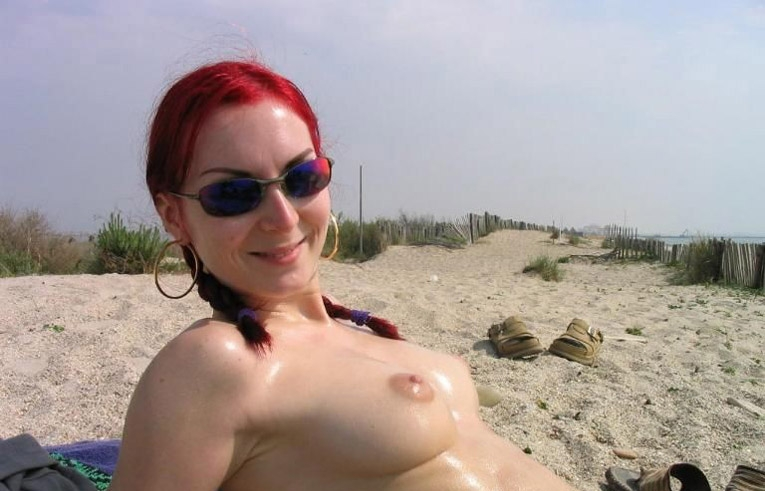 Redhead smiles for camera and shows off well oiled tits
