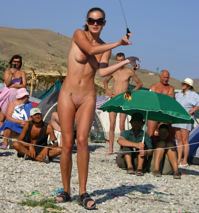 Tanned woman shows off shaved pussy for crowd - Nubile Babes